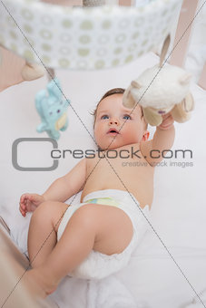 Adorable baby playing with toys in crib