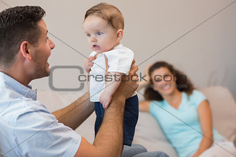 Happy man playing with cute baby