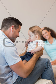 Happy man playing with baby
