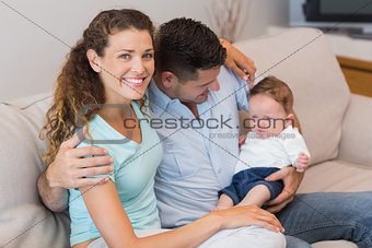 Happy woman with man holding baby