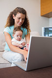 Baby with mother using laptop