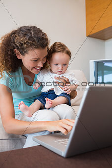 Mother showing laptop to baby