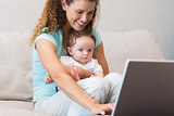 Mother using laptop while holding baby