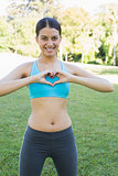 Woman in sportswear showing heart shape