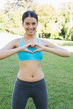 Woman in sportswear showing heart shape