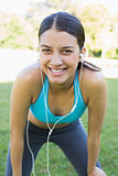 Portrait of happy fit woman listening music
