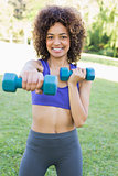 Woman lifting dumbbells in park
