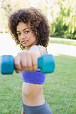 Confident woman lifting dumbbell
