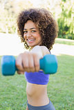 Smiling woman lifting hands weights