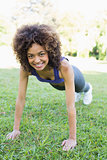 Happy woman doing push ups in park