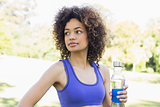 Thoughtful sporty woman holding water bottle