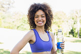 Happy fit woman holding water bottle