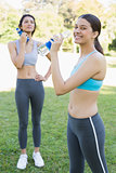 Sporty women drinking water in park
