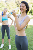 Fit women drinking water in park