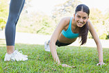 Smiling woman doing push ups in park
