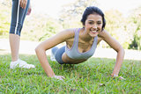 Beautiful woman doing push ups in park