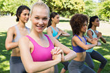 Smiling woman exercising with friends