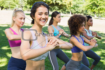 Beautiful woman exercising with friends