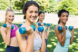Happy multiethnic women lifting dumbbells