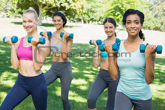 Confident sporty women lifting weights