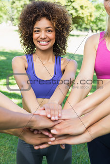 Happy young fit woman stacking hands with friends