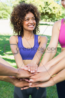 Young sporty woman stacking hands with friends