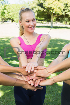 Fit woman stacking hands with friends