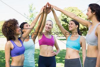 Women in sportswear raising hands in park