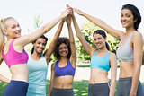 Women in sportswear raising hands in park