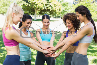 Women stacking hands in park