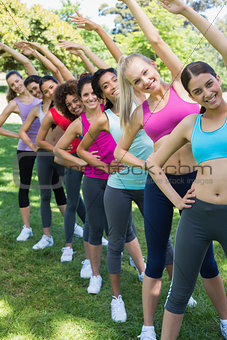 Women performing stretching exercise at park