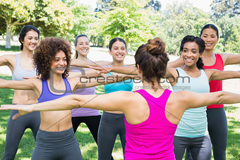 Women exercising with instructor at park