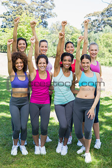 Happy sporty women clenching fist at park