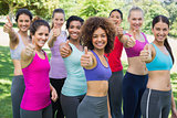 Sporty women gesturing thumbs up in park