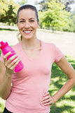 Sporty woman holding water bottle in park