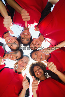 Soccer team gesturing thumbs up while forming huddle