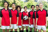 Female soccer team with ball at park