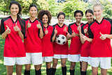 Female soccer team gesturing thumbs up at park