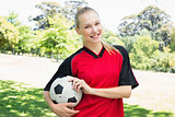 Confident female soccer player at park