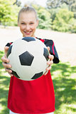 Female soccer player showing ball at park