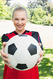 Beautiful soccer player showing ball at park