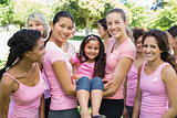 Women carrying girl during breast cancer awareness
