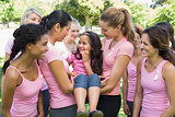 Volunteers carrying girl during breast cancer campaign