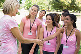 Participants shaking hands during breast cancer awareness
