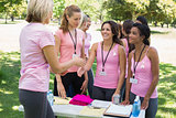 Volunteer greeting participants during breast cancer awareness