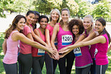 Female breast cancer marathon runners stacking hands