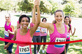 Breast cancer participants crossing finish line at race