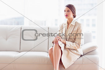 Thoughtful businesswoman sitting on sofa