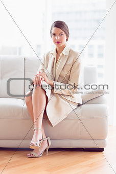 Thoughtful businesswoman sitting on sofa looking at camera