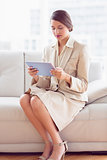 Thoughtful businesswoman sitting on sofa looking at tablet pc